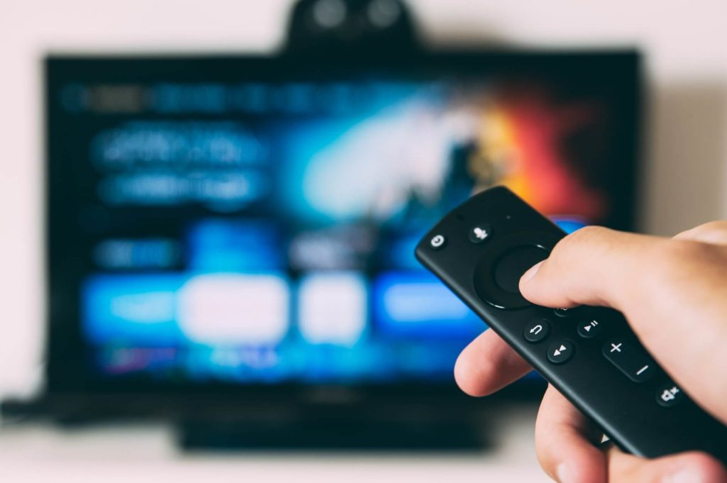 Person holding the remote and watching online streaming video